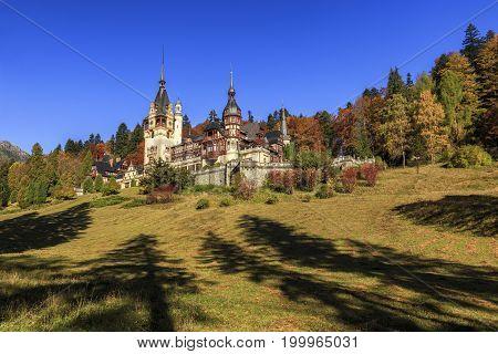 Amazing famous royal castle and ornamental garden with majestic autumn colors, Peles castle, Sinaia, Transylvania, Romania, Europe