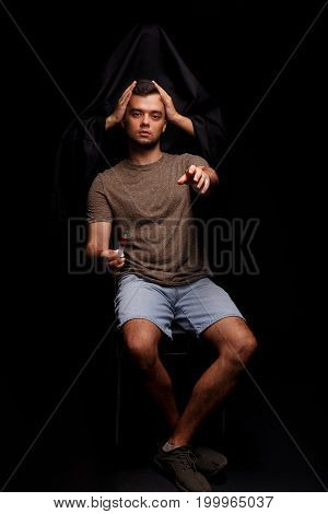 Death holding guy's head on a black background. An addict, narcomaniac with a syringe stretches his hand towards the camera. A young man fighting with drug addiction. Addiction treatment concept.