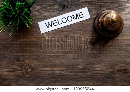 Check in at the hotel. Word welcome near service bell on dark wooden table background top view.