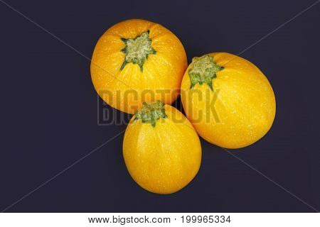 A view from above of three bright yellow zucchini on a purple background. Ripe, raw colorful zucchinis for natural juices or smoothies. Healthy vegetables for various vegetarian snacks. Copy space.