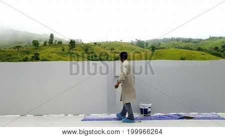 Painter painting to cover landscape picture of mountainsMale painter working with concentrated expression on a beautiful mountains landscape painting.