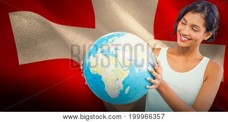 Smiling woman holding globe  against digitally generated swiss national flag