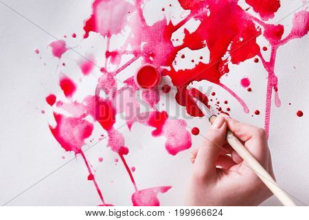 Artist creating watercolor painting. Brush and paint jar in female hands. Bright red drops on paper texture. Modern art backgroung with copy space