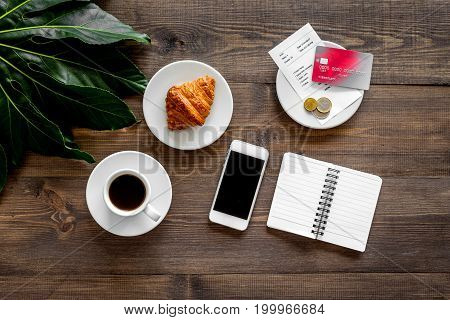 Restaurant bill and bank card near cup of coffee and bakery on dark wooden table top view.