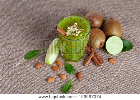 A view from above of an organic composition of a pile of kiwi, juicy lime and a slice of apple on a light brown background. Healthy cocktail from exotic fruits full of nutritious vitamins on a fabric.