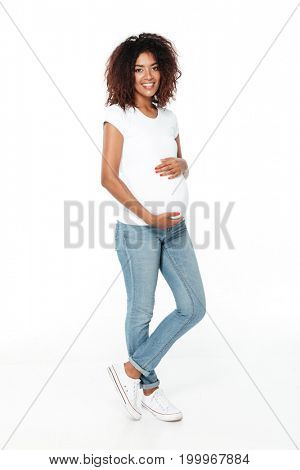 Picture of happy young pregnant african woman standing isolated over white background. Looking camera.