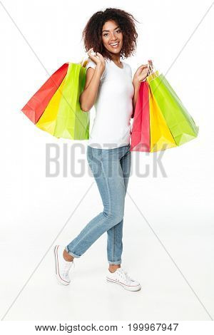 Image of happy young african woman standing isolated over white background. Looking camera holding shopping bags.