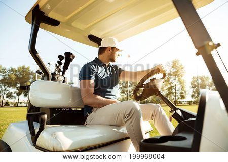 Male golfer driving a cart with golf clubs bag along green course