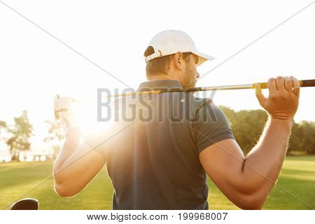 Back view of a young man carrying golf club while standing on field