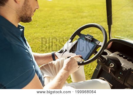 Cropped image of a male golfer sitting in a golf cart and using tablet computer