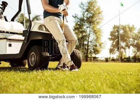 Cropped image of a male golfer leaning on a cart and holding golf club outdoors