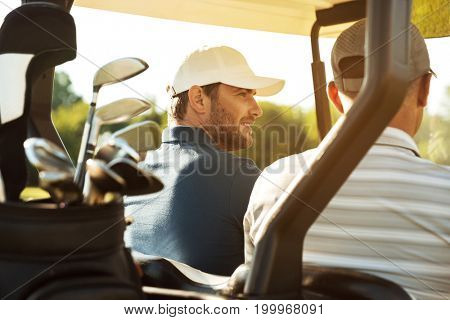 Two male golfers sitting in a cart and talking