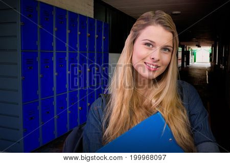Pretty student in the library against purple lockers in corridor