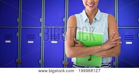Portrait of smiling young woman with file against purple closed lockers in school