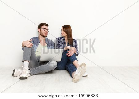 Couple discuss something with laptop on the lap. Happy man and woman sitting on the floor in white interior of their new apartment