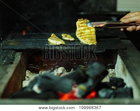 Close-up of juicy pieces of grilled chicken. A male hand turns nutritious meat on a blurred grid background. Tender smoky fillet with firewood. Outdoors, nature, cooking concept. Copy space.