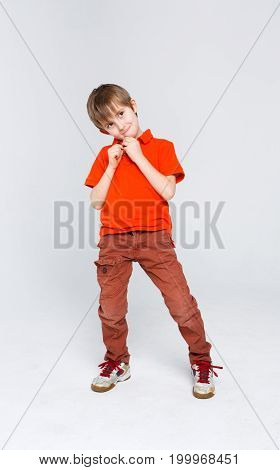 Portrait of funny mischievous boy in bright casual clothes at white studio background, copy space