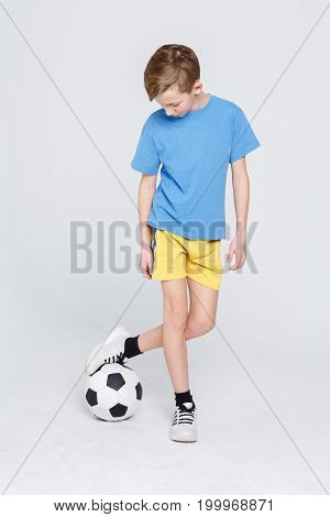 Young football player. Handsome boy in sportswear playing with soccer ball over white studio background. Active and sporty lifestyle concept. Vertical, copy space