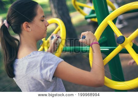 Young smiling girl does exercises at simulator for hands in park