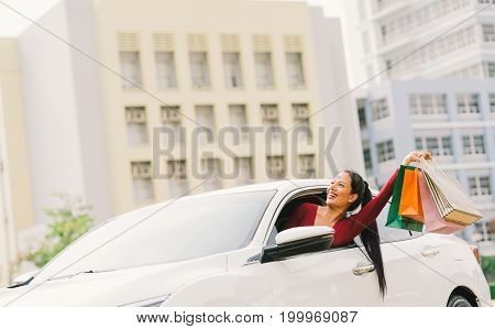 Happy Asian tourist woman raise shopping bags on modern white car look up at copy space. Shopaholic consumerism activity retail shop hobby holiday travel or casual shopper urban lifestyle concept