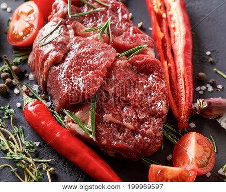 Raw rib eye steak with herbs, spices and vegetables. Ingredients for healthy restaurant meals. Fresh meat, salt, rosemary and thyme, chilli, cherry tomatoes, garlic on stone black background, closeup