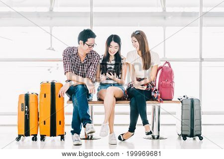Group of young Asian travelers using smartphone checking flight or online check-in at airport together with luggage. Travel abroad summer holiday trip or mobile phone application technology concept