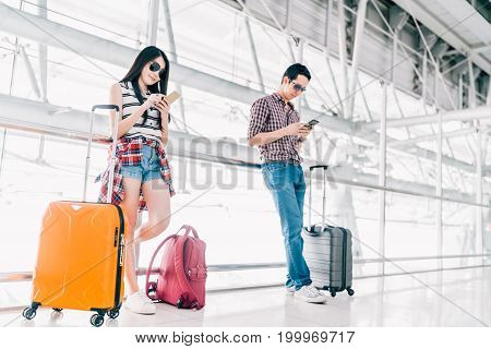 Young Asian man and woman using smartphone checking flight or online check-in at airport together with luggage. Air travel summer holiday or mobile phone application technology concept