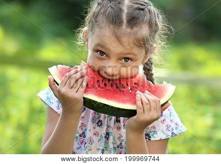 Beautiful Kid Girl Eating Big Red Watermelon With Fun Humor Look On Summer Day Green Glass Backgroun