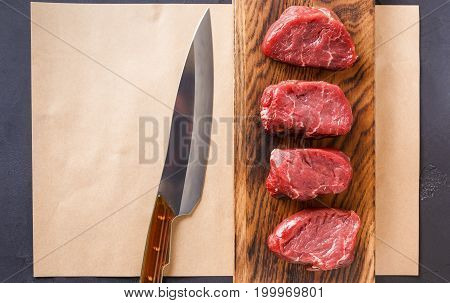 Raw filet mignon steaks. Slices of fresh beef meat on wooden cutting board on black table at craft paper background. Organic ingredients for restaurant meals and sharp chef knife, top view, copy space