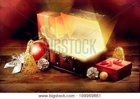 Opened Chest With Light, Gift And Other Christmas Decoration On Old Wooden Table