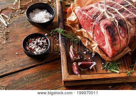 Raw black angus beef bound with rope in craft paper on cutting board. Aged prime marble meat, herbs and spices rustic wood background with copy space