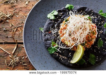 Exclusive restaurant food. Traditional hawaiian appetizer - poke with fresh salmon on black sesame flat cake on gray plate. Healthy meals in modern serving on wooden table background, copy space