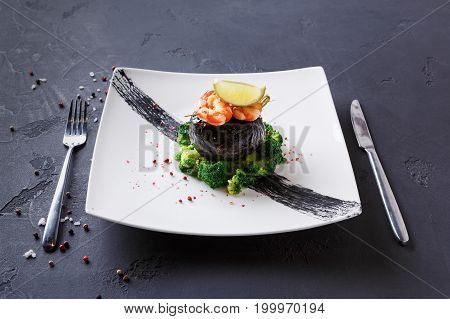 Excuisite restaurant food. Dorado fillet wrapped in nori on broccoli with shrimps and lemon piece on top. Served on white platter, sprinkled with pepper salt, on black background, copy space