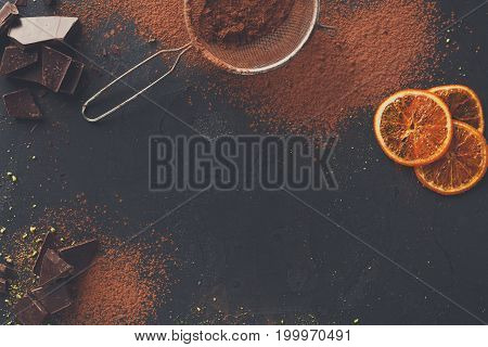 Sweet background. Cocoa powder in a sieve and sprinkled on surface, orange citrons and chocolate pieces on black slate. Top view, copy space