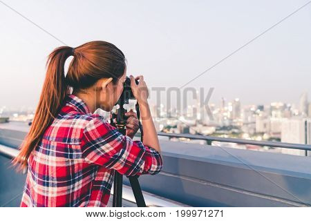 Long hair Asian woman taking cityscape photo on building rooftop in low light situation. Photography or hobby concept. With copy space