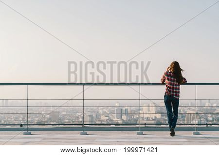 Woman using mobile phone at rooftop during sunset with copy space communication or lonely people concept