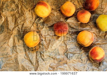 Ripe peaches are scattered on newsprint. view from above
