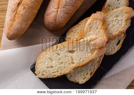 French homemade baguette bread. Wheat baguette on black shale. cut baguette on the wooden table.