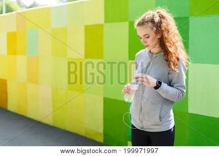 Young woman runner is having break, with bottle of water after jogging, colorful background