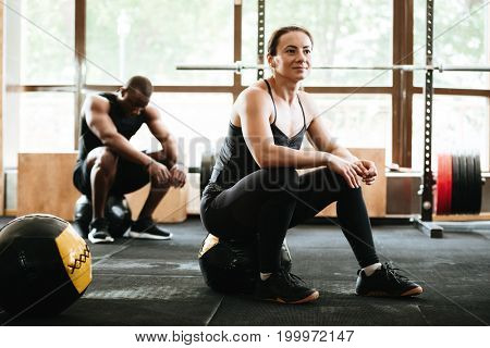 Picture of group of multiethnic sports strong people make sport exercises with ball in gym.