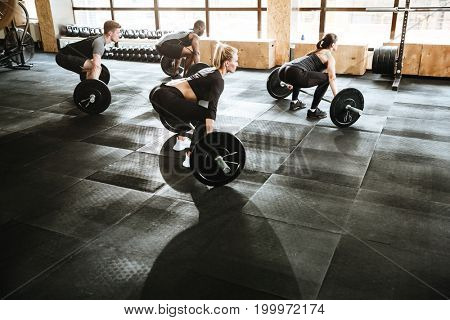 Group of multiethnic sports strong people make sport exercise with barbell.