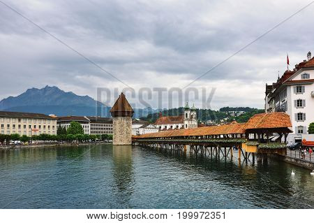 Lucerne Switzerland - June 14 2017: Historic city center of Lucerne with Famous Chapel bridge Lake Lucerne and Pilatus mountain on background at sunrise