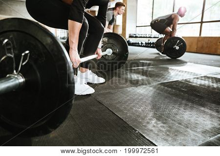 Cropped image of group of multiethnic sports strong people make sport exercise with barbell.
