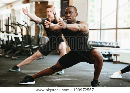 Picture of group of sports strong people in gym make sports exercises. Looking aside.