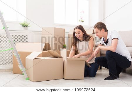 Young couple unpacking moving boxes in new apartment, copy space