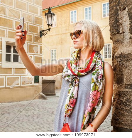 Charming female with funky look making photo on cell telephone while standing near architectural monument in urban setting, woman traveler photographing on mobile phone interesting objects outdoors.