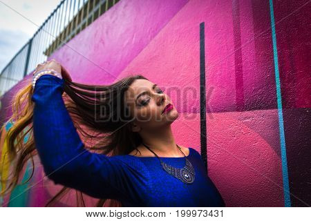 Beautiful young girl walking in the city with colorful abstract wall background