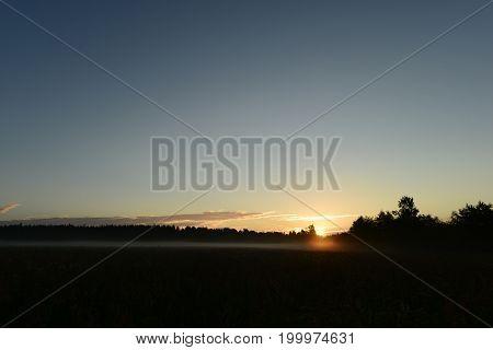 Dawn of sunrise the first sunshine through a foggy summer haze on the field