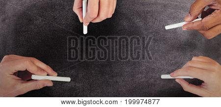 Cropped hands of people holding chalks against black background
