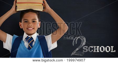 Smiling schoolboy carrying books on head over white background against black background